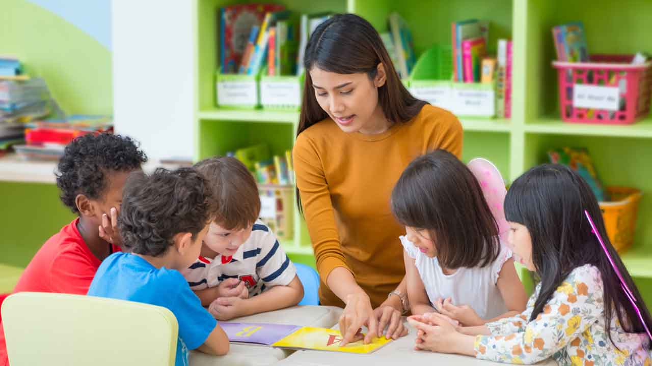 preschool teacher surrounded by students at table