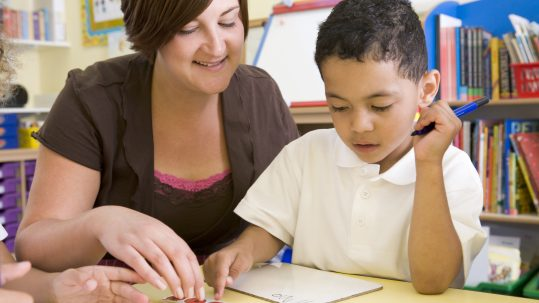 Teacher helping young boy learn numbers
