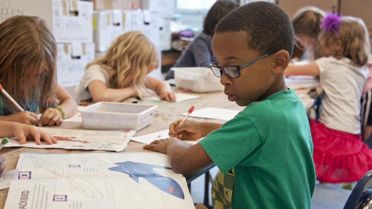 Black boy writing at school desk.