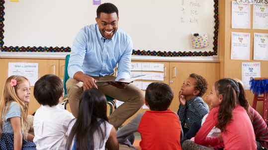 Black male teacher reading to young students